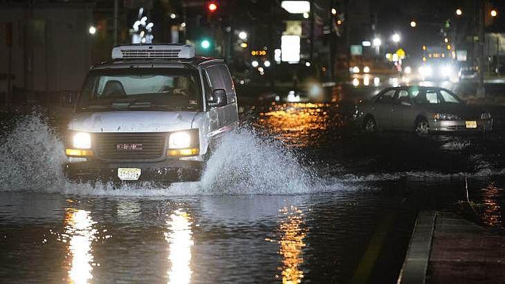 Motorista de van passa por área parcialmente alagada em Teterboro, Nova Jersey