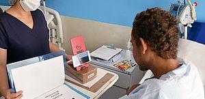 Terapeuta Ocupacional acompanha paciente em aula online durante recuperação no hospital